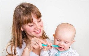 Young mother brushing baby's teeth