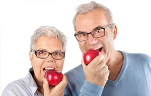 Senior man and woman eating red apples