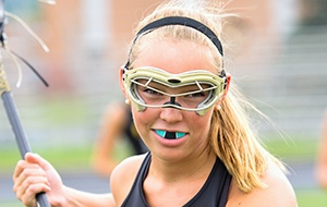Teen girl playing lacrsse with blue mouthguard
