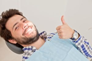 Man with thumb's up in dentist's chair