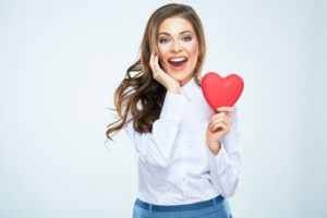 woman holding heart smiling