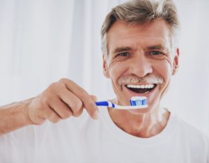 older man about to brush his dental implants