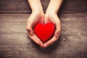 Outstretched hand holding heart shape without gum disease