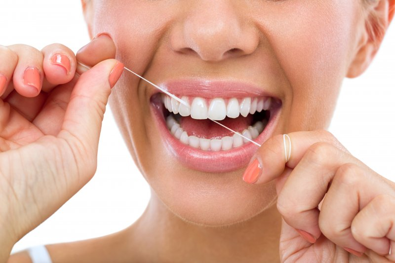 Woman smiling and flossing her teeth
