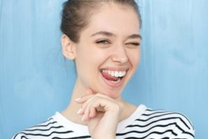 Woman standing in front of a light blue background wearing a striped shirt smiling