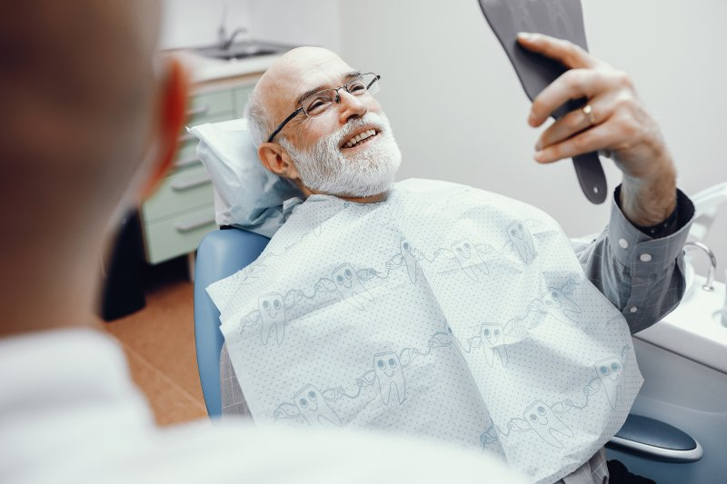 Patient in dental chair smiling with dental implants