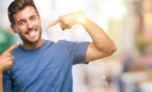 man pointing to his smile after seeing his cosmetic dentist